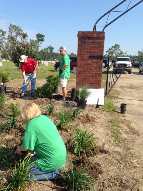 Stephanie Hutchins, chair of Keep Mississippi Beautiful's board of directors, plants shrubs near one of the cemetery's entrances with Michael Belote with Southwest Distributors and Forrest Dungan of Columbia.
